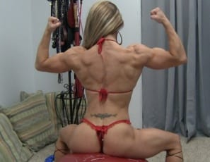 Professional female bodybuilder Maria G uses a big red ball to show off her vascular biceps