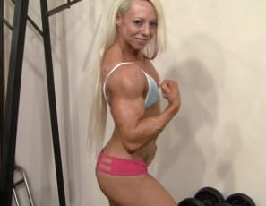 Female bodybuilder Nathalie Falk works her triceps in the gym, shows off her big, vascular biceps, and poses to show you the mature muscles of her ripped pecs, legs, glutes, and  tattooed abs.