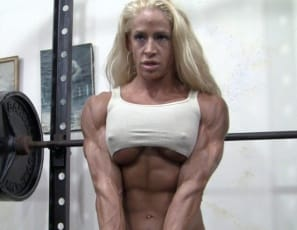 Professional female bodybuilder Jill Jaxen's in the gym, squatting in gold panties to work her muscular legs and glutes, and posing to show you her tattooed, vascular biceps, powerful pecs and ripped abs. Then she asks, Want to feel my quads? Well, do you?