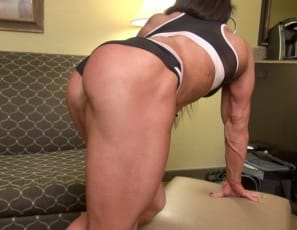 Professional female bodybuilder Carla is posing for you on the couch, showing off her vascular  biceps, powerful pecs, ripped abs, tattooed legs,  and muscular glutes and calves. You might want to sit down.