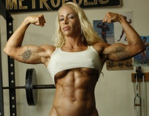 Professional female bodybuilder Jill Jaxen poses for you in the gym, wearing gold botty shorts, lying on a gold bench, and impressing you with the ripped muscles of her pecs, legs,  glutes, calves and vascular abs. That's one golden girl.