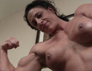 Tattooed female bodybuilder Miss Lisa's posing completely nude for you, showing you her vascular biceps, ripped legs and glutes, muscular pecs, and shoulders like boulders.  You want to come train with me? she asks. I promise to hurt you.