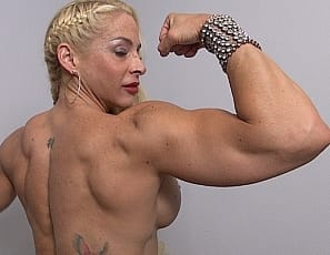 Female bodybuilder Jill Jaxen is fanning herself because it's so hot. She strips down until she's not wearing anything but her ultra-high-heeled shoes, and poses so you can see her ripped abs, vascular biceps, powerful pecs, tattoos, and muscular legs and glutes...