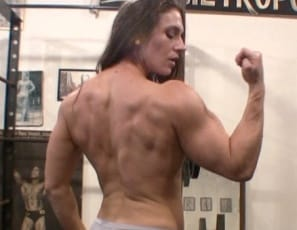 Female bodybuilder Andrea G does bench presses in the gym