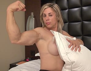 Mature female bodybuilder Extreme Thule is in the bedroom, taking off her high-heeled shoes and wiggling her bare feet, posing, flexing her biceps and showing off the muscles of her abs, legs, and tattooed glutes and pecs. Those are some extreme muscles.