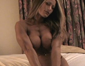 Female Bodybuilder Nikki poses in the bedroom in her tiny g-string and shows off her muscles – her biceps, flat abs, powerful pecs, and gorgeous glutes. She also shows off her sexy tattoo.