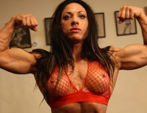 Female bodybuilder Ripped Vixen displays her awesomely ripped and tattooed muscles as she poses in the gym. Check out her vascular biceps, abs and legs, her perfect pecs and her very vixenish naked kitty.