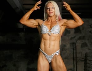Female bodybuilder Nathalie Falk poses for you in the dungeon, showing you her ripped abs, vascular biceps, the mature muscles of her legs and glutes, and her tattoo. She's powerful from every angle.