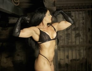 Professional female bodybuilder Jane Santos makes her first appearance here at SheMuscle, and she does it by showing off her amazing physique in our dungeon. What else did you expect from her? Jane shows off her powerful biceps, her long strong legs, shapely calves, and amazing glutes. Wearing high heeled shoes and posing with leather gloves, whips, and chains we think Jane looks right at home being the dungeon master!