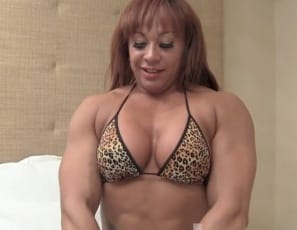 Female bodybuilder Rita takes off her panties and poses naked for you in the bedroom in high-heeled shoes, showing off her muscular pecs and biceps and her tattooed abs, back, glutes, legs, and muscle control.