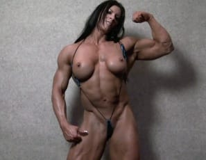 "Barefoot in the bedroom, bodybuilder Angela Salvagno poses naked for you and taunts you, saying ""Feel how hard I am"" as she touches her muscled pecs, her huge, vascular biceps, and her massive legs, glutes and calves. ""You want to touch it, don't you?"" she asks. That would mean both of you are feeling hard."